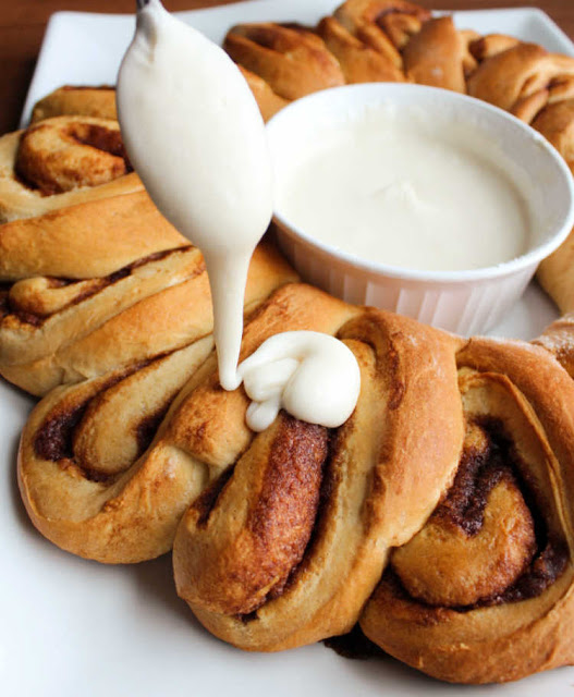 spoon drizzling icing over warm cinnamon rolls