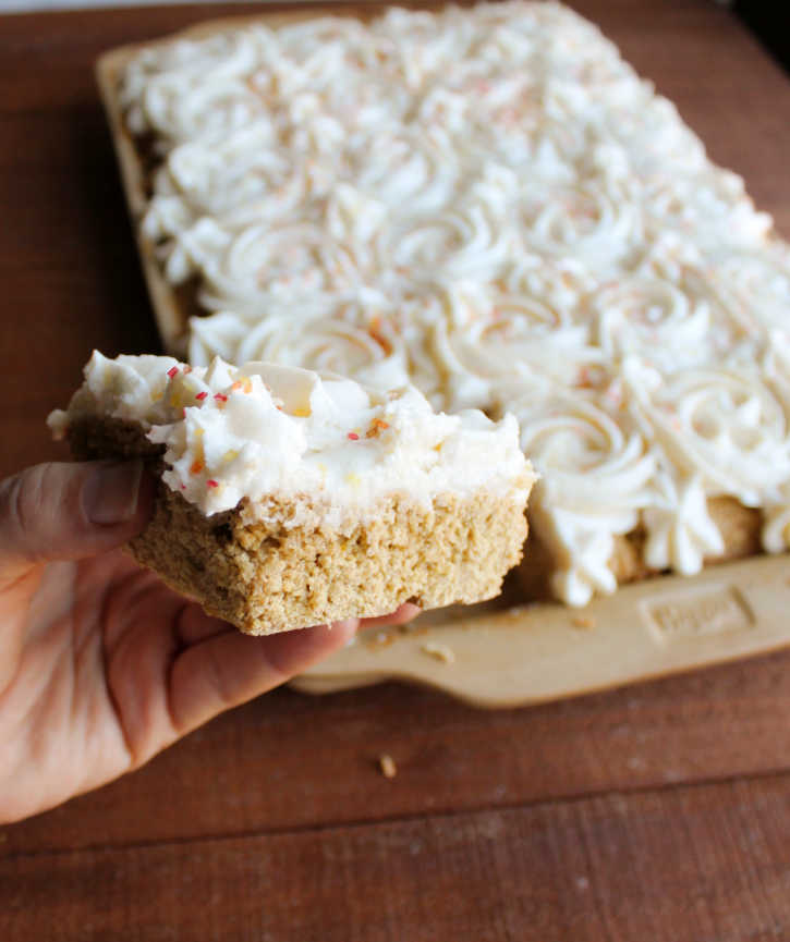 hand holding square of pumpkin cookie bar with frosting rosettes on top.