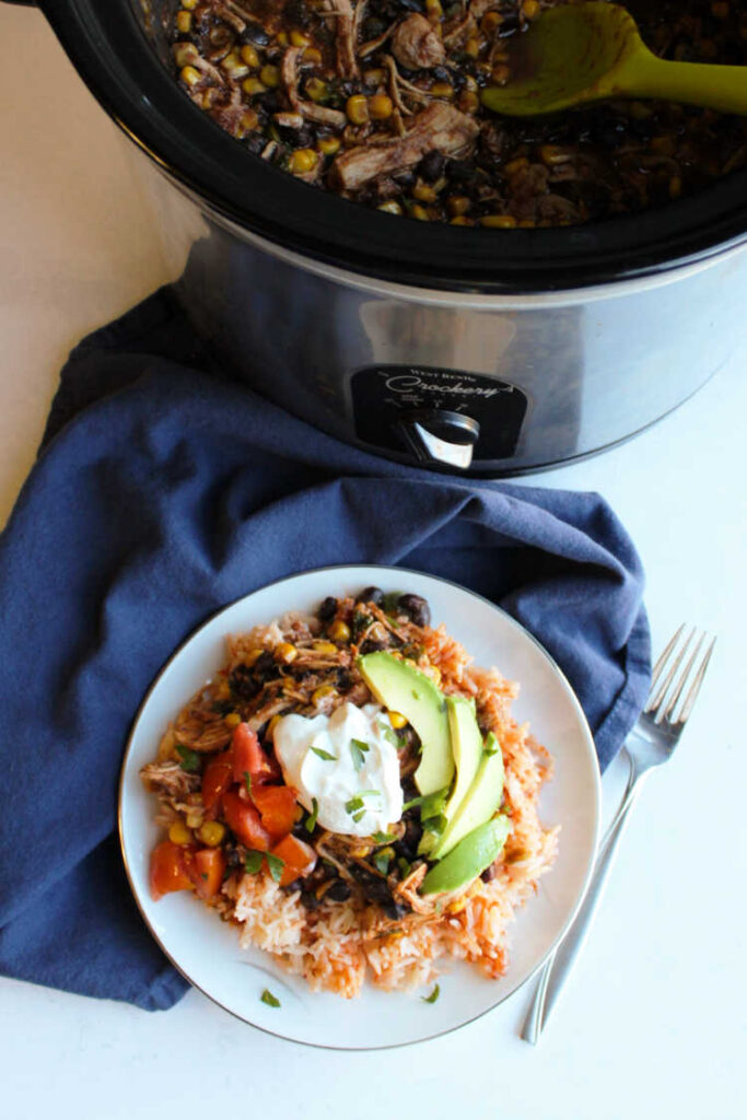 slow cooker full of salsa chicken by burrito bowl.