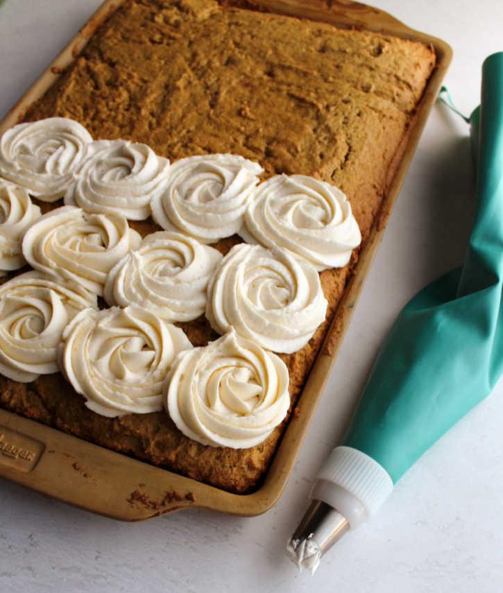 tray of pumpkin spice bars with piping bag of buttercream putting rosettes on top.