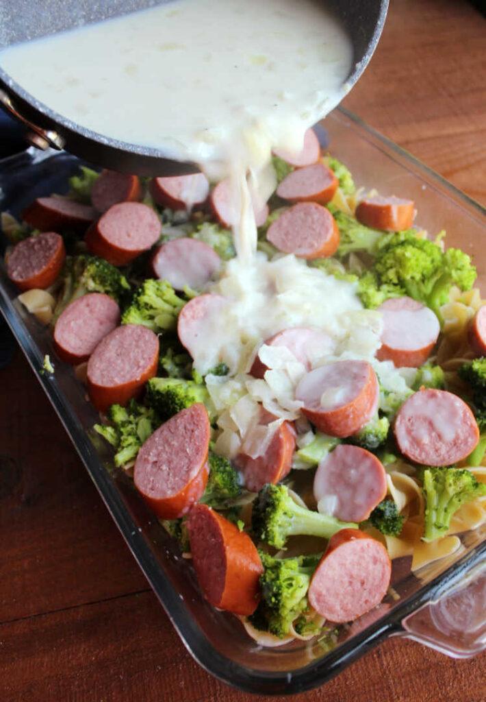 pouring gravy mixture over pasta, kielbasa and broccoli in casserole dish.