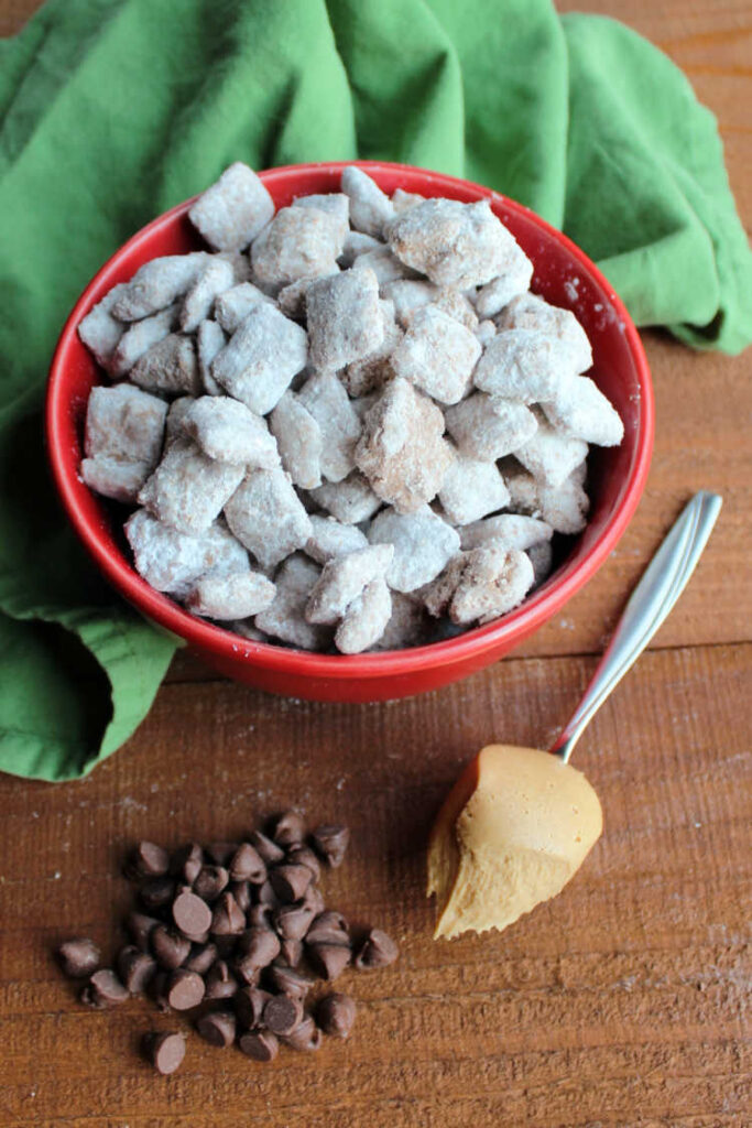 bowl of muddy buddies with a spoonful of peanut butter and pile of chocolate chips.