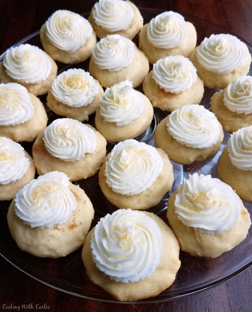 Plate of soft rounded sour cream cookies topped with buttercream frosting.