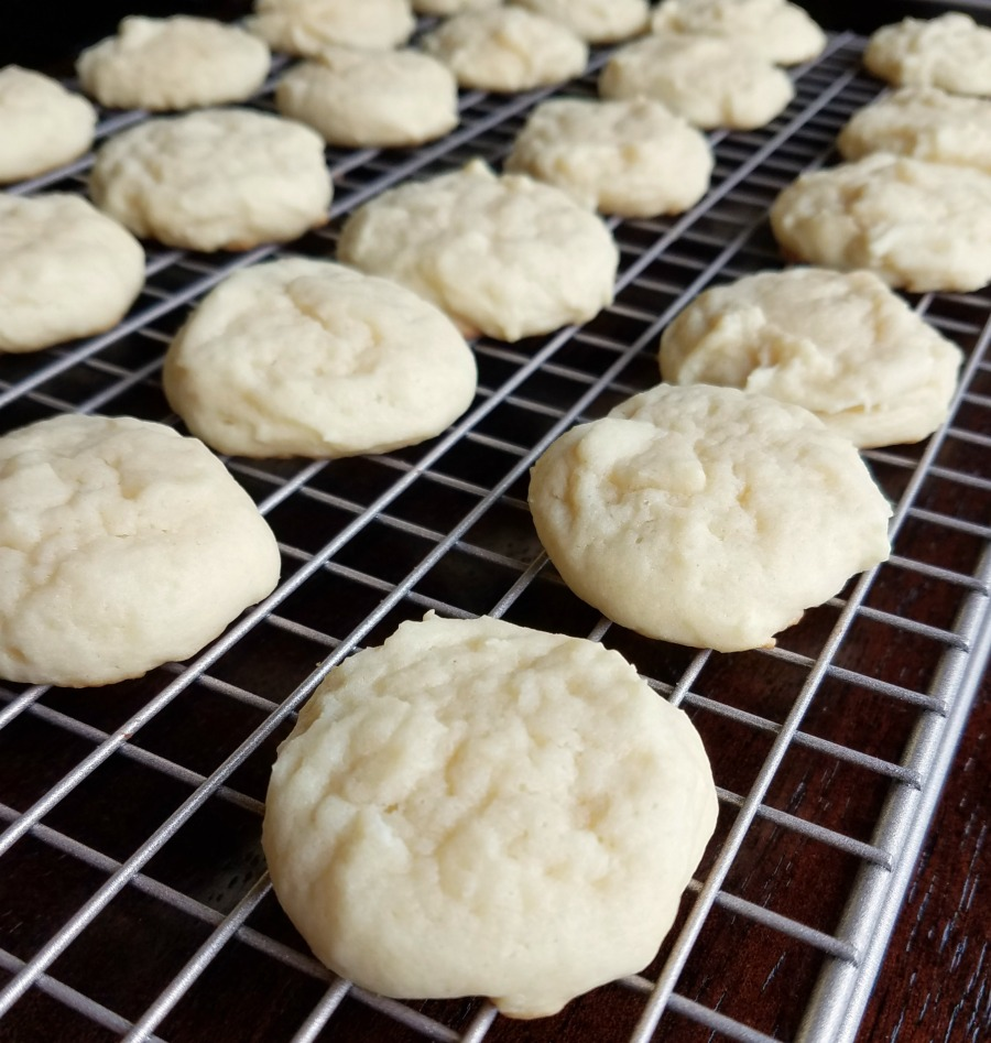 soft round sour cream cookies on cooling rack.