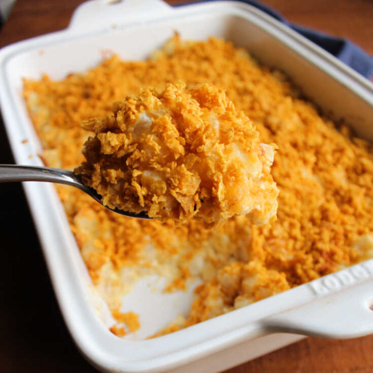 spoon lifting out a serving of cornflake topped cheesy potato bake