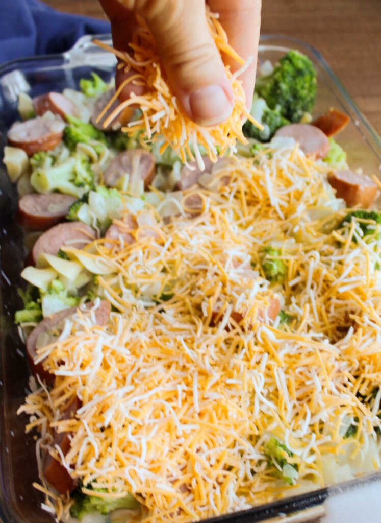 sprinkling cheese over broccoli, pasta and sausage.