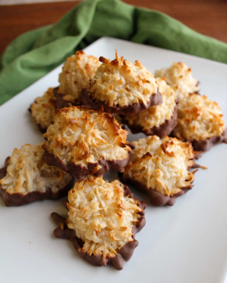 pile of chocolate dipped coconut macaroons on tray.