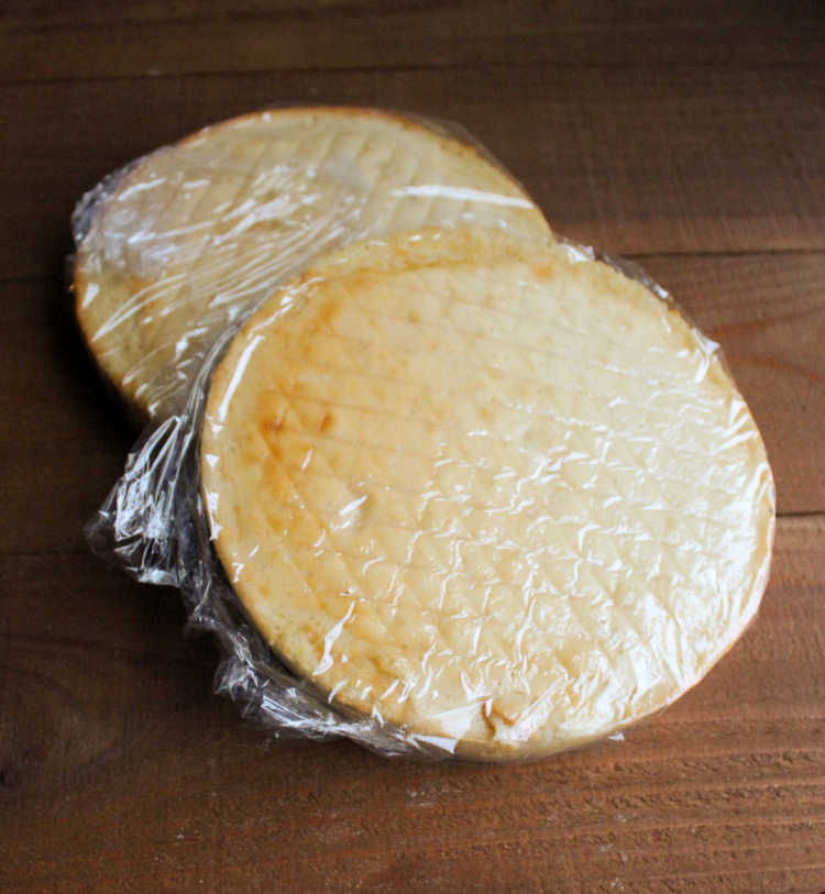 two round white cake layers wrapped in plastic wrap.