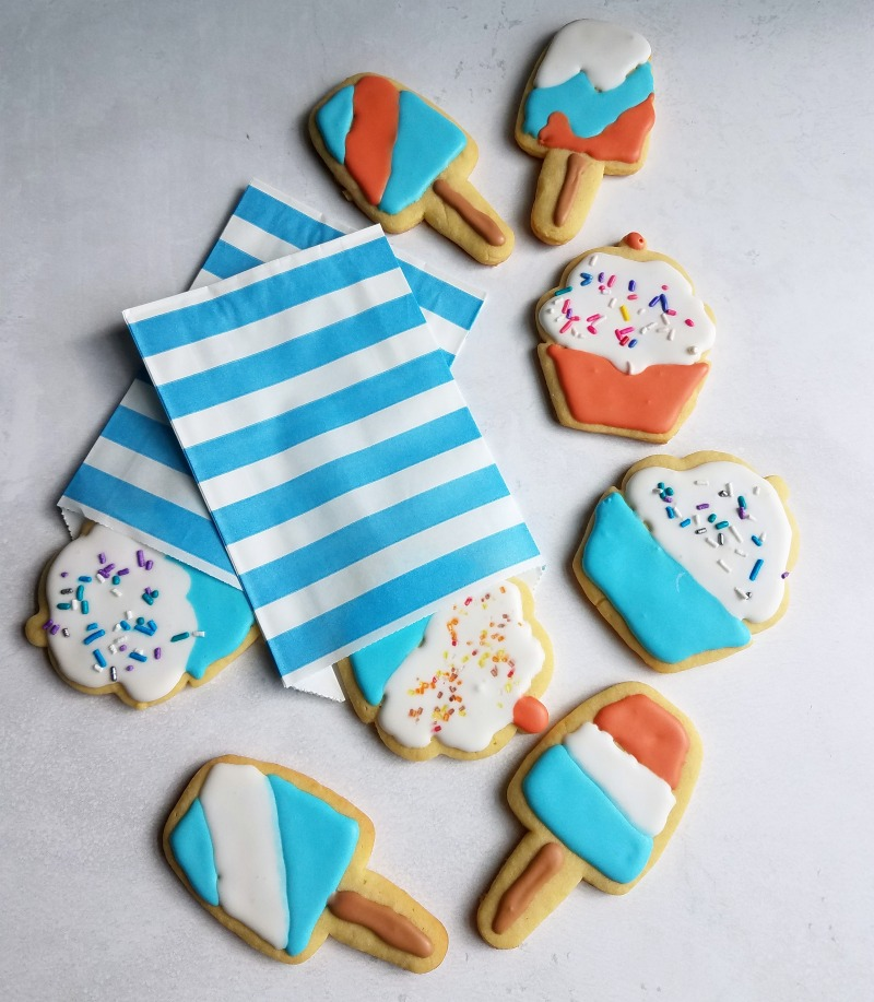 Sugar cookies shaped like cupcakes and pospsicles decorated with red white and blue royal icing and sprinkles.
