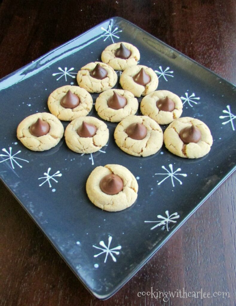 chew peanut butter blossom cookies topped with chocolate kisses arranged to look like Christmas tree.