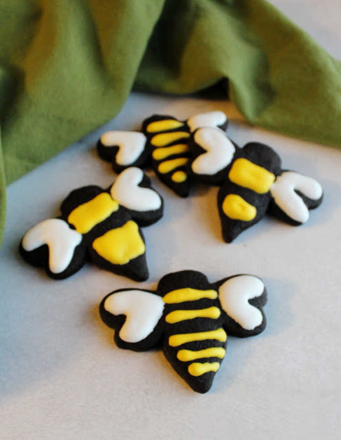 black cookies cut in the shape of bees and decorated with yellow and white royal icing