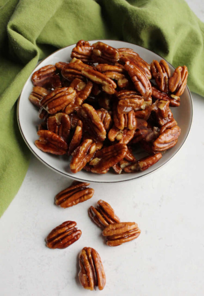 honey coated pecans spilling out of bowl.