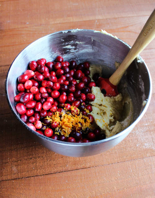 mixer bowl filled with batter, fresh cranberries and orange zest ready to be mixed