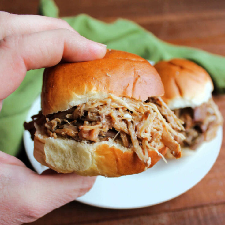 hand holding slider piled high with pineapple pulled pork