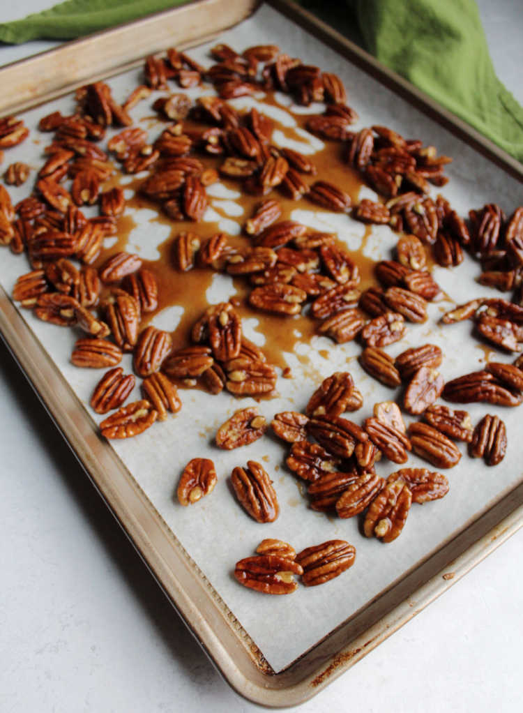 honey coated pecans cooling on parchment paper.
