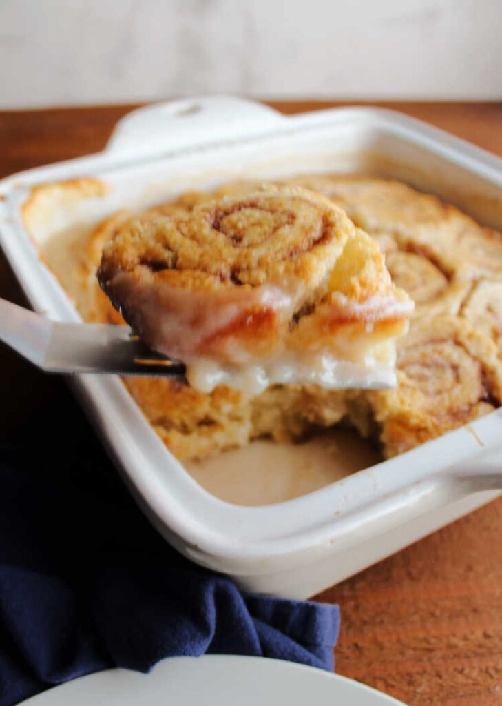 lifting gooey cinnamon butter roll out of pan.