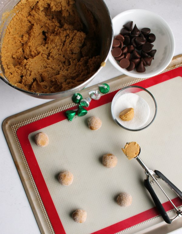 bowl of peanut butter cookie dough being rolled into balls to become blossom cookies.