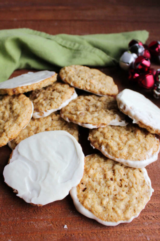 pile of white chocolate dipped frostbite cookies with jingle bells in the background.