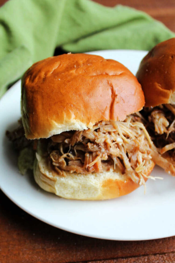 Asian style pineapple pulled pork sandwich on plate.