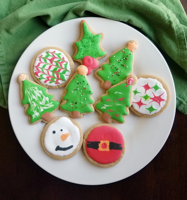 plate of peanut butter cookies cut into Christmas shapes and decorated with royal icing
