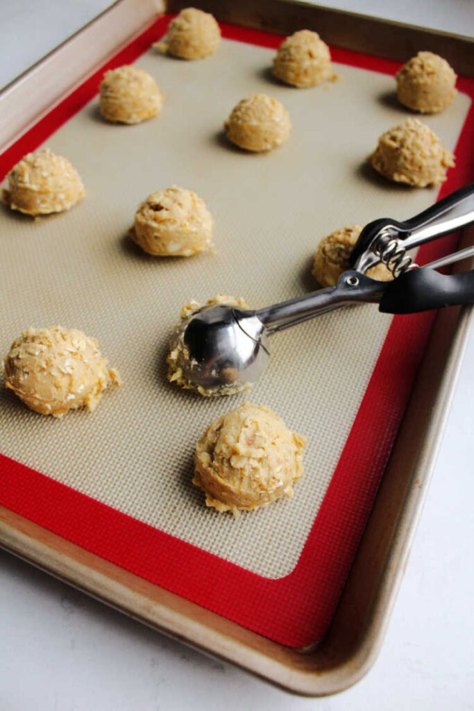 small cookie scoop with balls of dough on silicone mat lined cookie sheet pan.