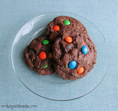 plate with three large chocolate cookies loaded with M&Ms