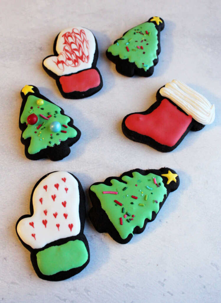dark chocolate cookies cut into Christmas shapes and decorated with royal icing.