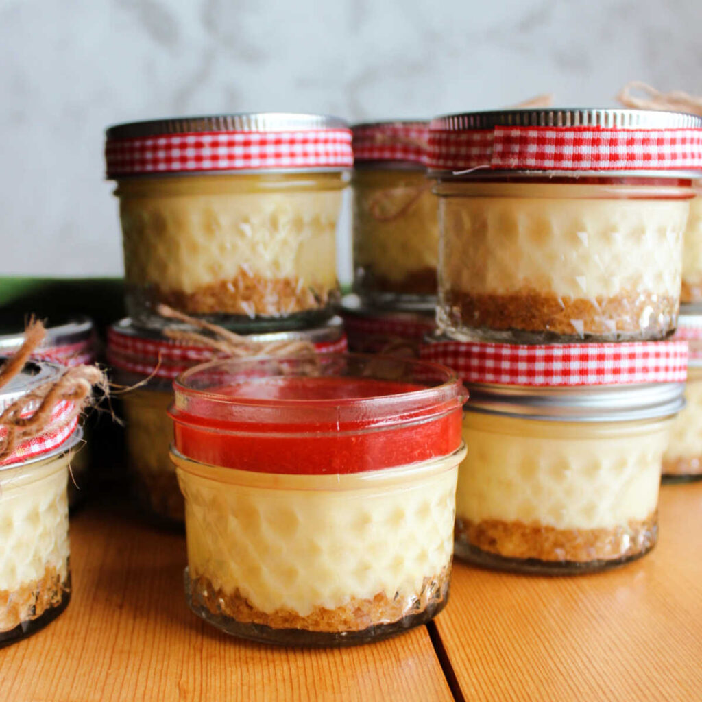 small glass jars filled with cheesecake and topped with strawberry topping