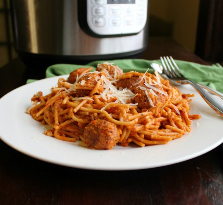 plate of creamy spaghetti and meatballs in front of instant pot