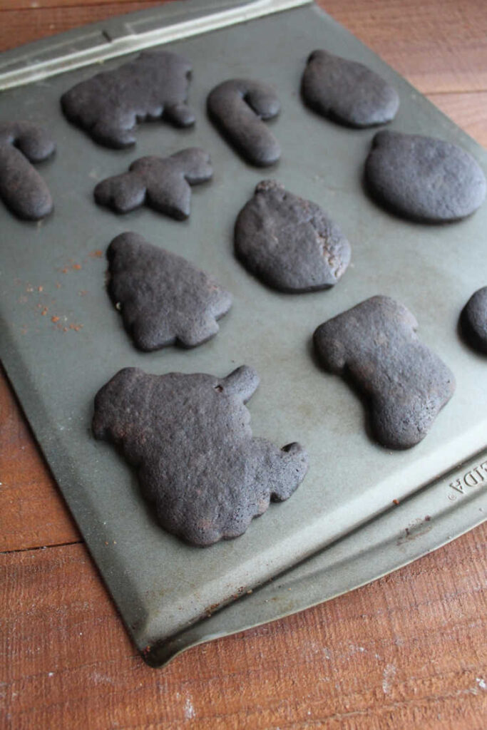black cookies cut into fun shapes on sheet pan.