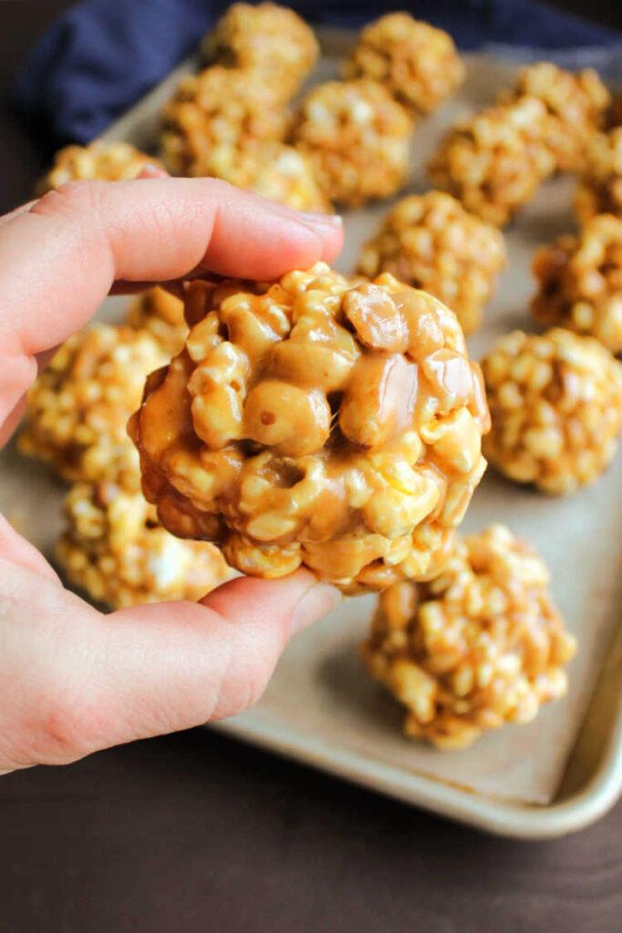 hand holidng peanut butter popcorn ball