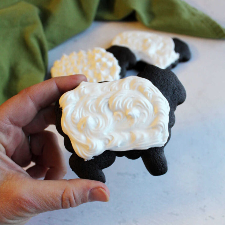 dark chocolate cookies in the shape of sheet with white royal icing fleece on top.