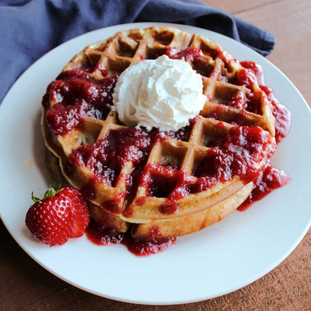 stack of sourdough waffles with strawberry sauce and whipped cream