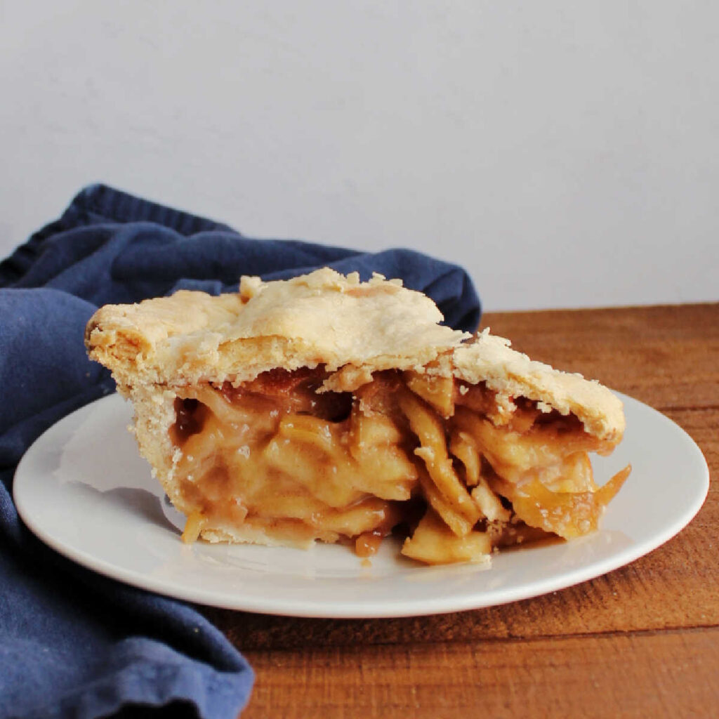 slice of apple pie with flaky crust, ready to eat.