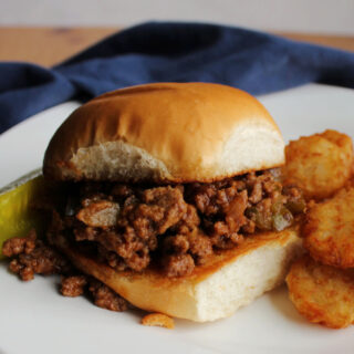 toasted bun filled with crumbly sloppy joe mixture with tater tots and a pickle on the side.