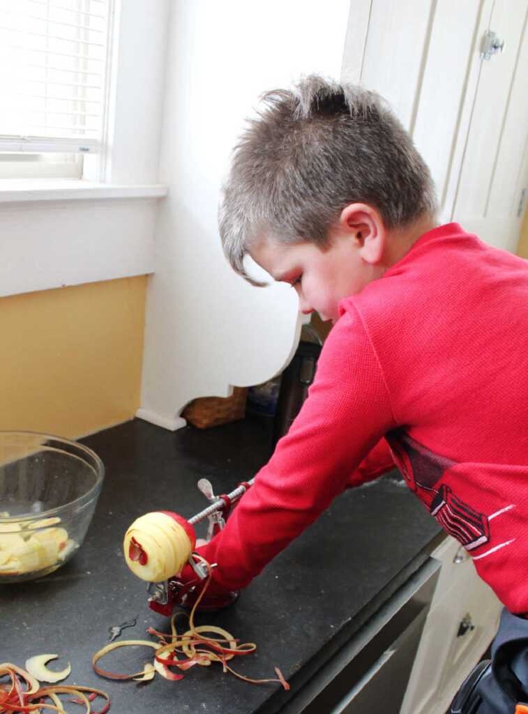 Little dude using the apple peeler, corer, slicer to get apples ready for pie.