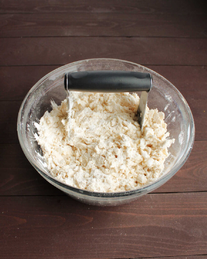 pastry cutter cutting lard into flour for pie crust.