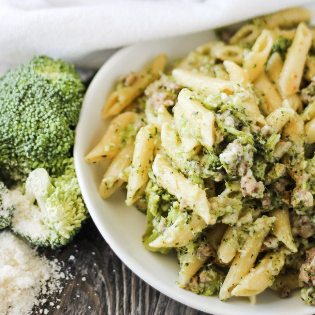 plate full of penne pasta with broccoli Italian sausage and Parmesan cheese ready to eat