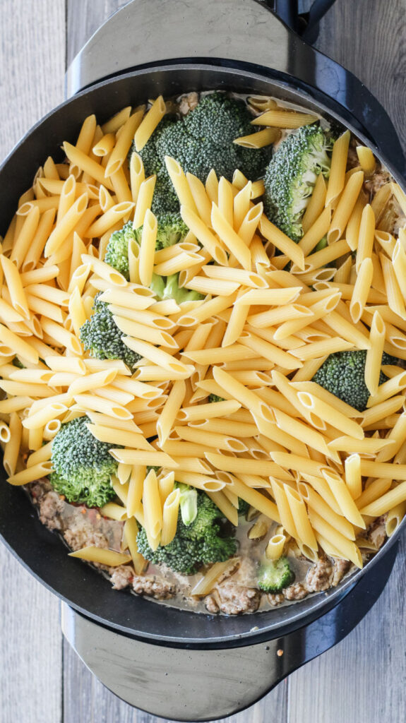 adding pasta and broccoli to pot with browned Italian sausage