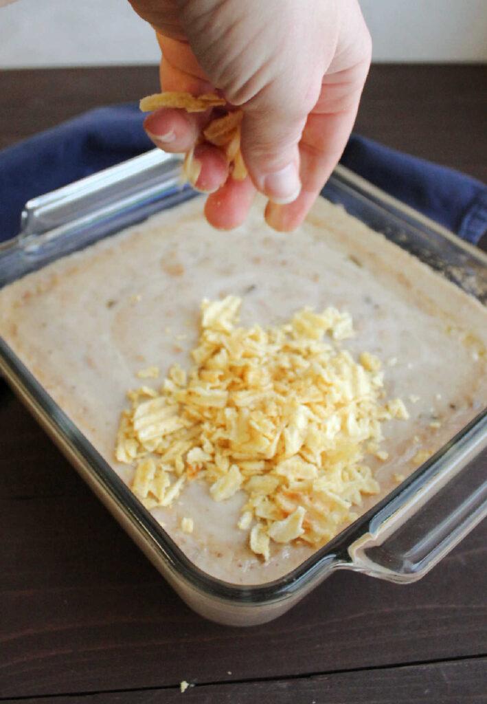 hand sprinkling potato chips over creamy tuna mixture.