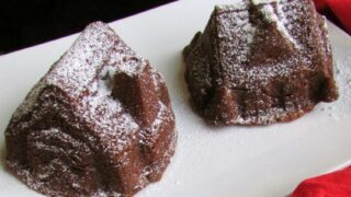 two small gingerbread house cakes on plate with powdered sugar dusting.