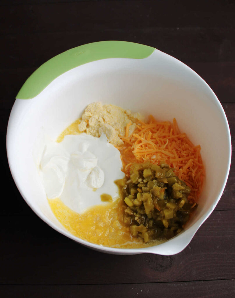 bowl full of corn pudding ingredients with green chiles, cheddar cheese, corn, sour cream, corn muffin mix, melted butter and more.