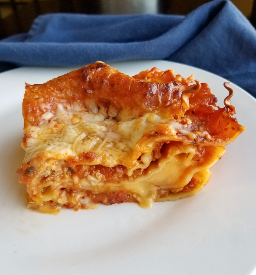 piece of american cheese lasagna with melty velveeta cheese layer in the middle.