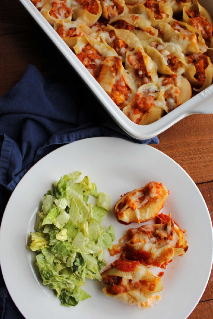 Chicken parmesan stuffed shells served on plate with a green salad.