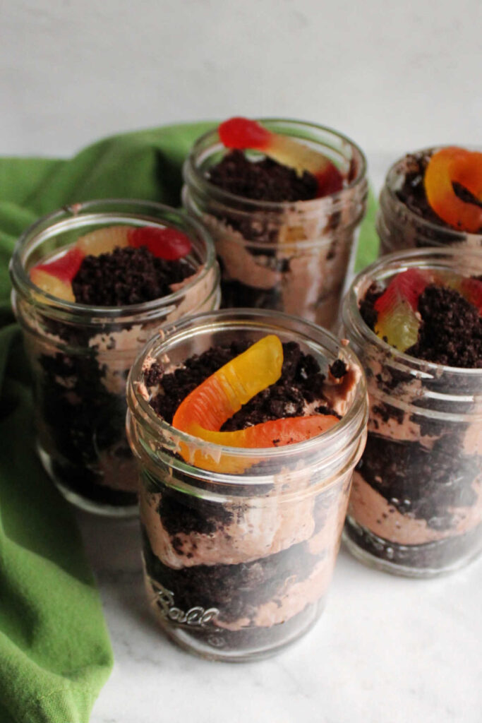 Jars of dirt pudding with layers of Oreo crumbs, chocolate pudding mixture and a gummy worm on top.