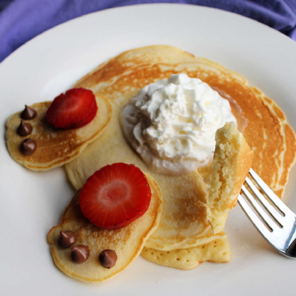 close up showing texture of homemade pancakes with bite on fork, whipped cream bunny tail and strawberry and chocolate chip bunny feet decorations visible in background.