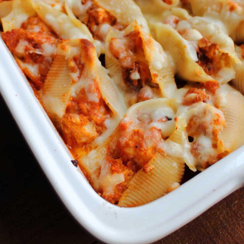 Close up on the corner of a pan of stuffed shells filled with chicken, tomato sauce and cheese.