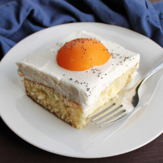 close square of vanilla sheet cake topped with white icing and apricot half to look like a fried egg.