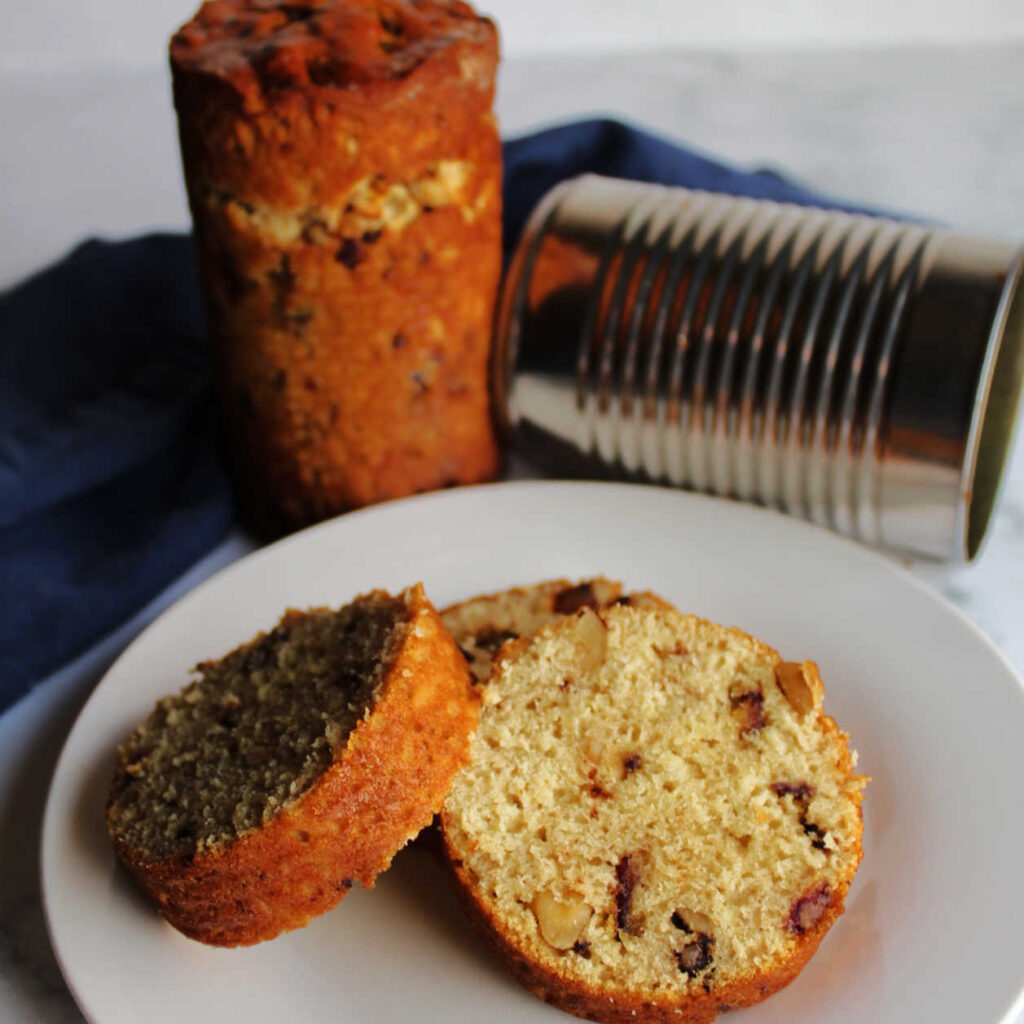round slices of date nut loaf on plate with can and bread in background.