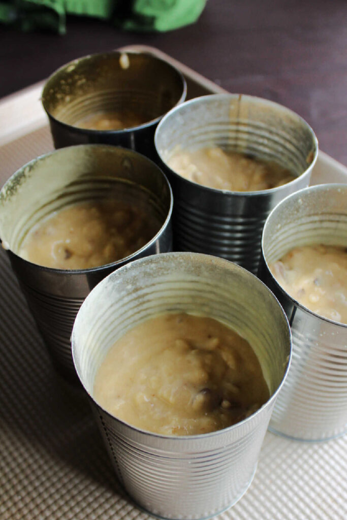 date walnut loaf batter in greased cans ready to bake.